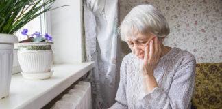 Heizkörper, Ältere Frau sitzt vor Heizkörper