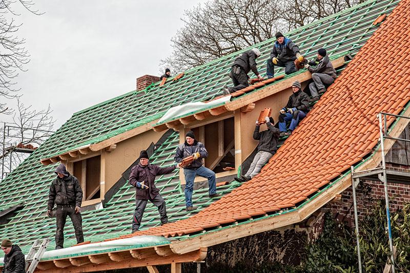 Nach alter Tradition halfen Nachbarn und Freunde bei der Dachdeckung.