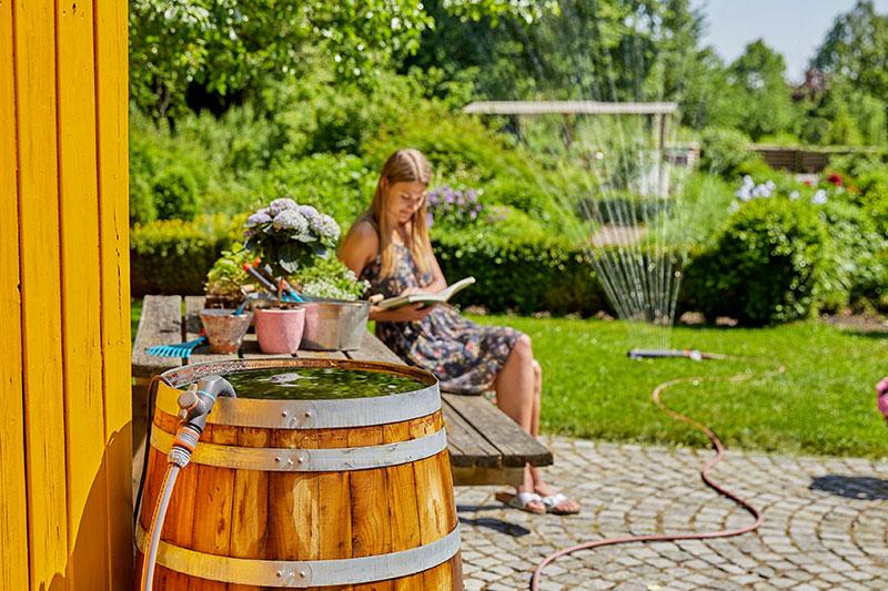 Kinderleichter Wassertransport von der Tonne in den Garten: Die GARDENA-Regenfasspumpe 4700/2 inox im Einsatz.
